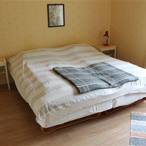 Dubbelsäng med två nattduksbord i rum med gula väggar.