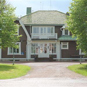 Framsidan Trunna Vandrarhem och konferens med grusväg fram till entrén och ett träd på var sida om vägen.