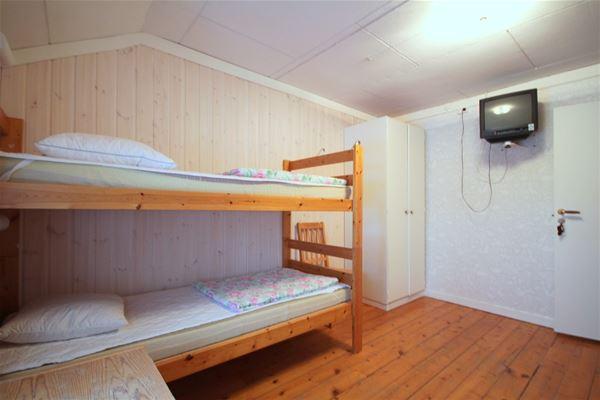 Rum med våningssäng och tv på väggen.
