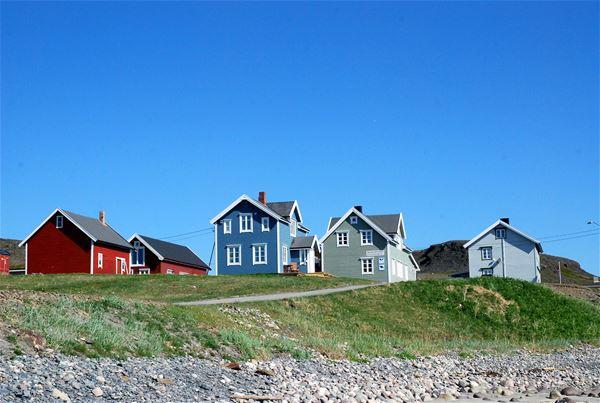 Bildet er tatt av Kongsfjord gjestehus. Nydelig solskinn på sommerstid. Husene som står der er i farger, blå, rød, grønn og grå.