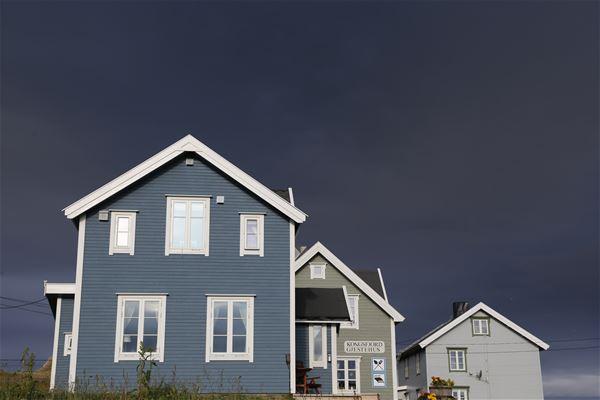 Bildet er tatt utenfor Kongsfjord gjestehus. Her vises et blått flott hus, å 2 grå hus i bakgrunnen.