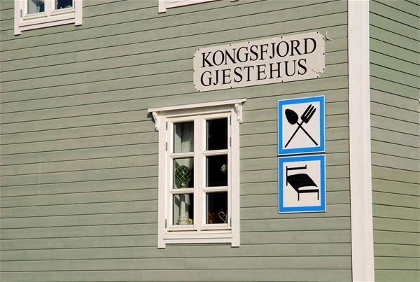 Her er det tatt bilde av noen skilt som henger på husveggen. Det er tenget til overnatting og mat. Det stor også Kongsfjord gjestehus på veggen.