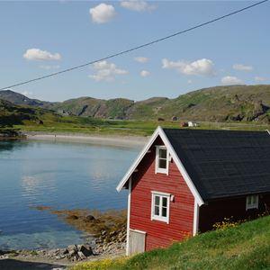 Bildet er av Månedskarbua i Kongsfjord som eies av Kongsfjord gjestehus. Det er et rødt lite sjarmerende hus nede ved brygga. Tatt overfor så man ser det stille havet og stranden i bakgrunnen.