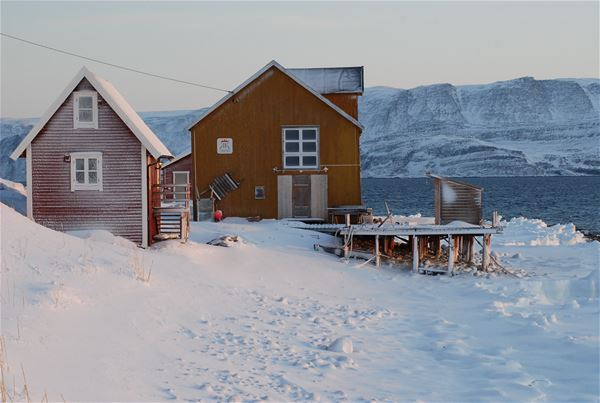Bildet er av Månedskarbua i Kongsfjord som eies av Kongsfjord gjestehus. Det er et rødt lite sjarmerende hus nede ved brygga. Bildet er tatt på vinterstid.