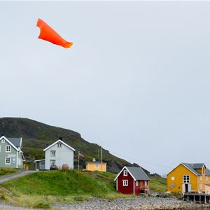 Bildet er av Månedskarbua i Kongsfjord som eies av Kongsfjord gjestehus. Det er et rødt lite sjarmerende hus nede ved brygga. Man ser å flere av husene som er i Kongsfjord, en en vimpel som flakser i vinden.