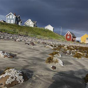 Bildet er av Månedskarbua i Kongsfjord som eies av Kongsfjord gjestehus. Det er et rødt lite sjarmerende hus nede ved brygga.