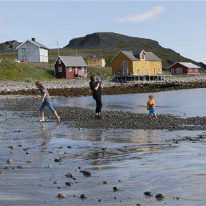 Bildet er av Månedskarbua i Kongsfjord som eies av Kongsfjord gjestehus. Det er et rødt lite sjarmerende hus nede ved brygga. Framme i bildet er det en familie å leker nede ved vannet på stranden.