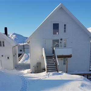 Bildet viser pakkhuset Lovisenborg i Kongsfjord tatt på vinteren. Det er hvit malt og sjarmerende å ligger på brygga. Bakgrunnen ser du havet og fjellene, nydelig blå himmel med skimt av sol lys.