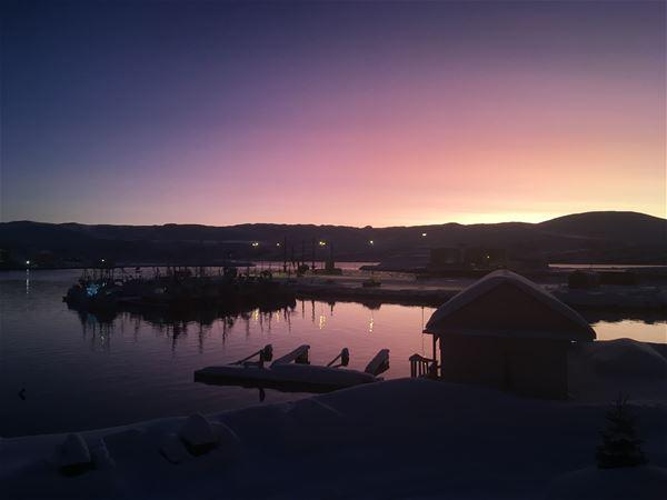 Bildet viser utsikten fra Båtsfjord brygge. Du ser utover havna, mot fjell. Det er helt mørkt på bildet med et hint av lilla lys, som lyser himmelen opp bak fjellene.