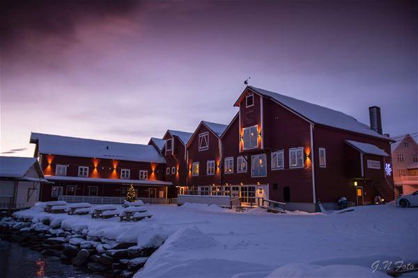 Bildet er tatt fra brygga uten for Båtsfjord brygge i Båtsfjord. Bygget er rødt og stort, stilen passer svært godt inn i fiskeværet. Bildet er tatt på vinterstid.