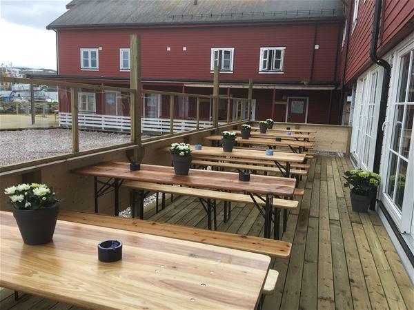 Bildet er tatt utenfor inngangen til bryggekanten pub, denne puben er i første etasje i Båtsfjord brygge. Her er det benker og bor, som du kan sitte ute å kose deg med noe godt å drikke.