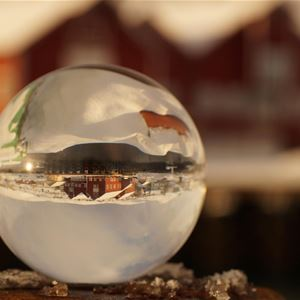 En liten glasskule med refleksjonen av Båtsfjord brygge i
