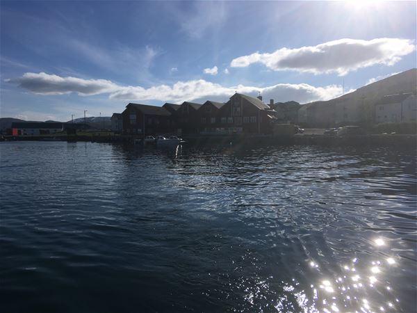 Bildet er tatt fra brygga uten for Båtsfjord brygge i Båtsfjord. Bygget er rødt og stort, stilen passer svært godt inn i fiskeværet. Bildet er tatt på sommeren.