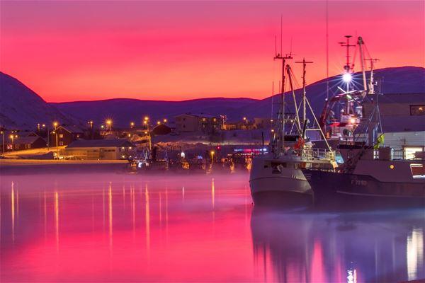 Bildet viser båter som ligger til kai i Båtsfjord. Det er helt rosa, lilla lys å masse frostrøyk på vinteren.