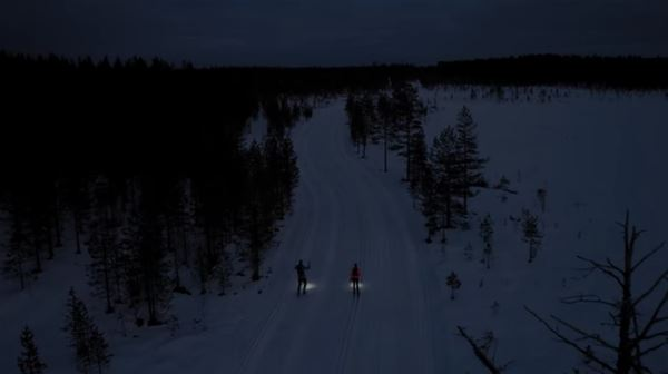 två skidåkare med pannlampor åker i spåret i mörker
