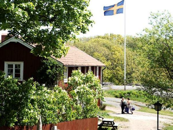 Idylliskt trähus och svenska flaggan
