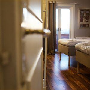 Öppen dörr till ett rum med två enkelsängar.