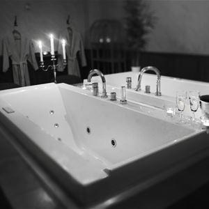Bubbelbadkar med en kandelaber, två vinglas och en hink med en vinflaska stående på badkarskanten.