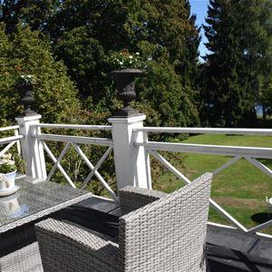 Balkong med utemöbler och utsikt över trädgården.