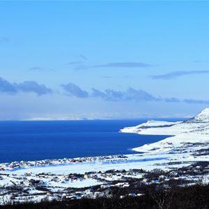 Utsikt over Vestre Jakobselv, som er dekket av snø i nydelig solskinn. Utsikten viser også havet å en nydelig lettskyet, blå himmel