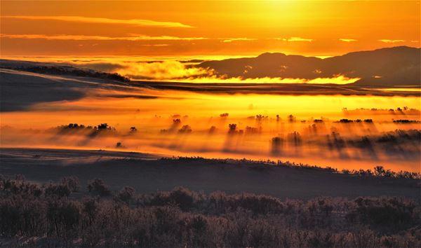 Solnedgang, med et sterkt oransje lys skinnende over det frostrøyk belagte landskapet. Trærne titter opp av forstrøyken. I bakgrunnen av bilde er det fjell.