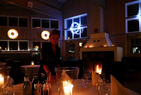 Nedsläckt restaurang med tända ljus och en brasa som brinner i öppna spisen.