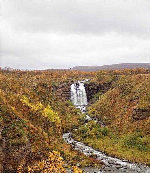 Bildet er av en foss på en nydelig høst dag, med alle høstens farger i marka