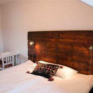 Dubbelrum med sänggavel av trä.