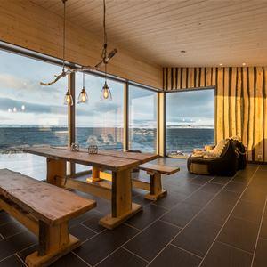 På innsiden av en av hyttene Varanger Lodge. Her er interiøret laget av naturlig tre. Du har en spektakulær, unik utsikt med glassvegger forran. Her ser du ut i Varangern`s åpne hav.