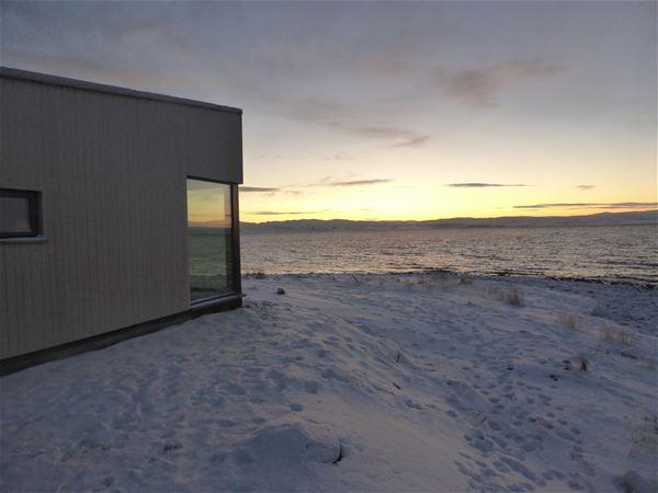 Varanger Lodge ligger i Nesseby. Her ser du hyttene fra nedsiden ute. Naturlig tre å store vinduer, med en spektakulær utsikt. Det er vintertid på bilde.