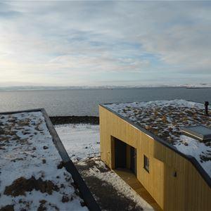 Her ser du Varanger Lodge oven fra å ut mot havgapet. Taket er dekket av gress. En unik å spektakulær utsikt