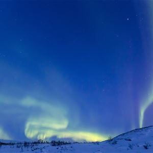 Nordlyset danser i alle farger over himmelen i vintermørket