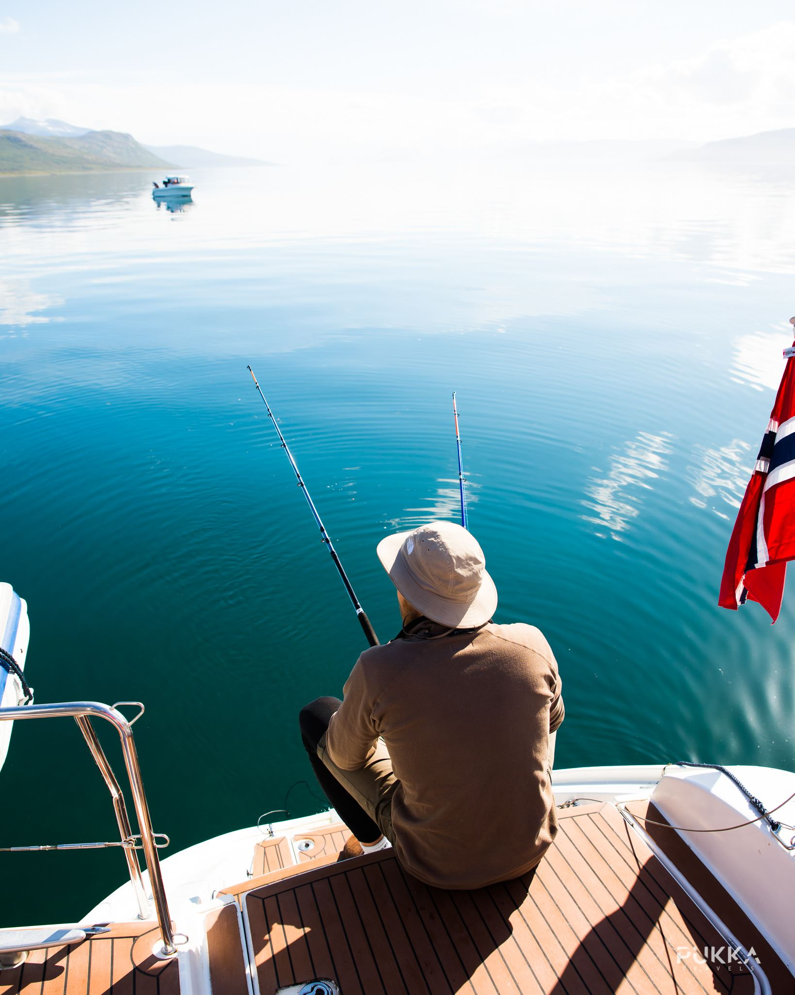 © Pukka Travels, Man sitting on the sunny deck fishing