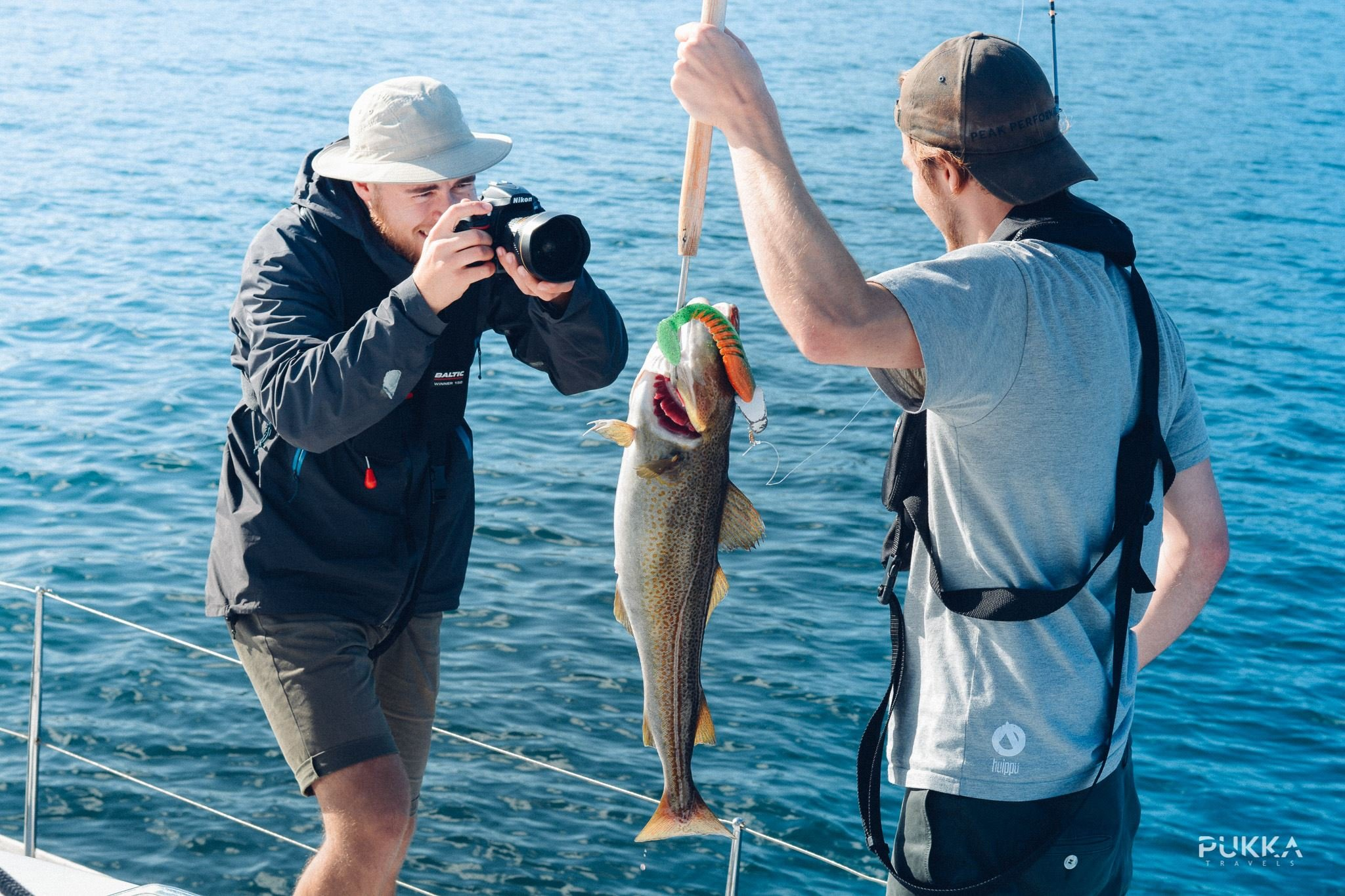 © Pukka Travels, Men having cought a fish and are taking photos of it
