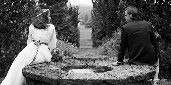 svart-vitt foto av ett bröllopspar vid en fontän.