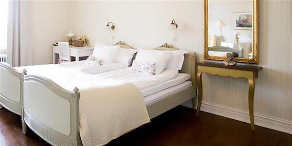 Dubbelsäng med ljusgrå sängram och en guldspegel med antikt bord under.