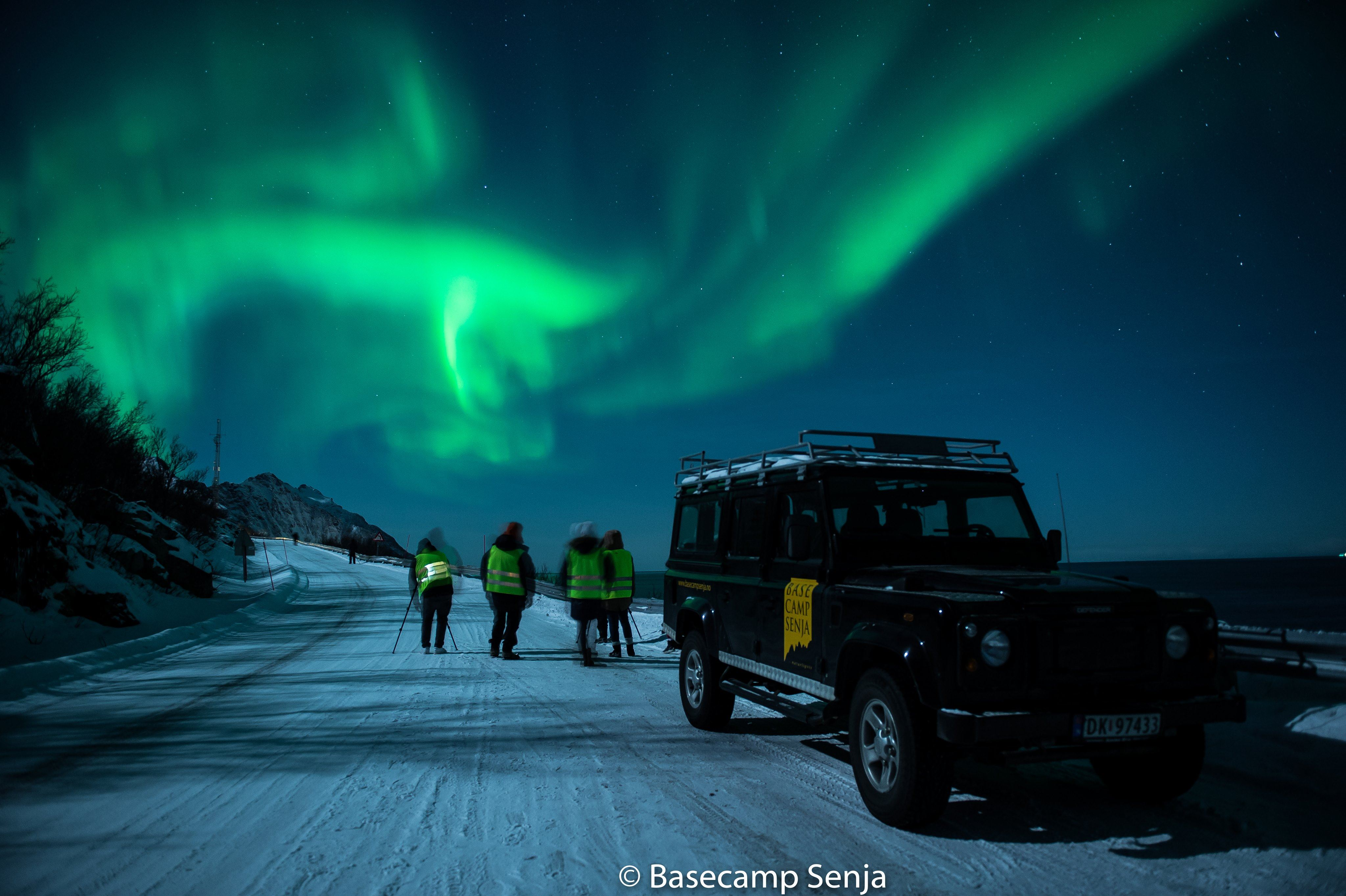 © Basecamp Senja, A truck parked on a snowy road with people and Northern Lights in the background