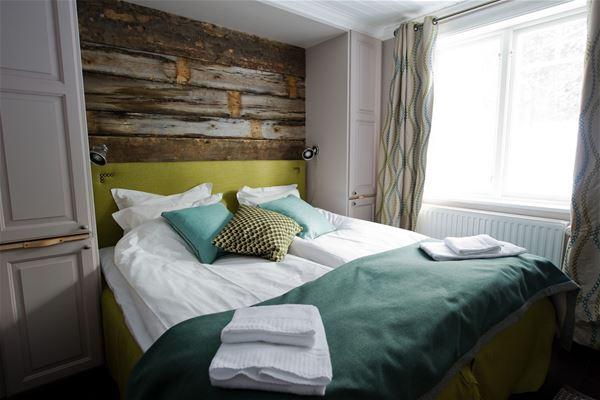 Dubbelrum. Grönt överkast på sängen. Furuvägg.