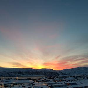 Bildet er tatt av Båtsfjord på vinterstid. Det er mørkt, men solen skinner bak fjellene i bakgrunnen.
