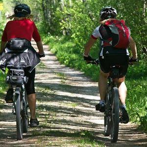Två personer som cyklar efter gusväg med skog omkring.