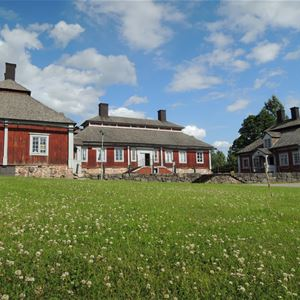Huvudbyggnaden med gårdshus på vardera sida.