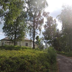 En uppfart upp till en gul byggnad bakom några träd.