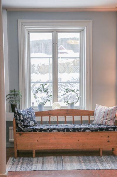 Gammeldags träsoffa med dyna intill fönster mot vätter ut mot Falu Gruva.