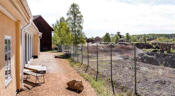 Baksidan av huset med ett stängsel som skiljer från kanten till Stora Stöten och det stora hålet.