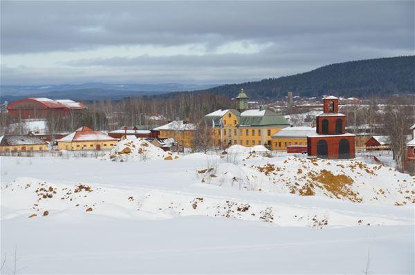 Snötäckt område med Falu Gruvas byggnader i bakgrunden.