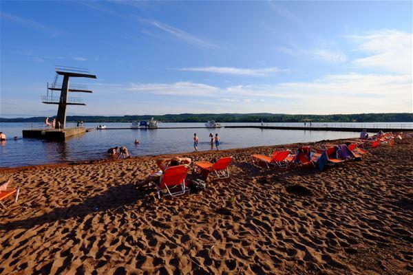 Stranden med orangea solstolar.