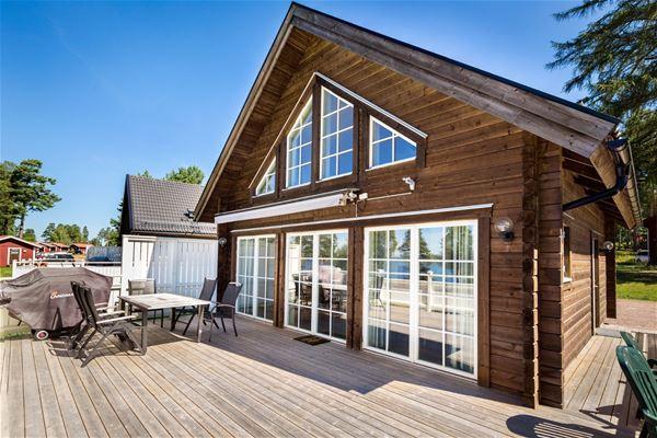 Stort brunt hus med stora fönster och altan.
