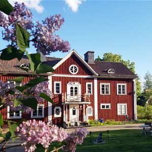 Exteriörbild på den rödmålade huvudbyggnaden.