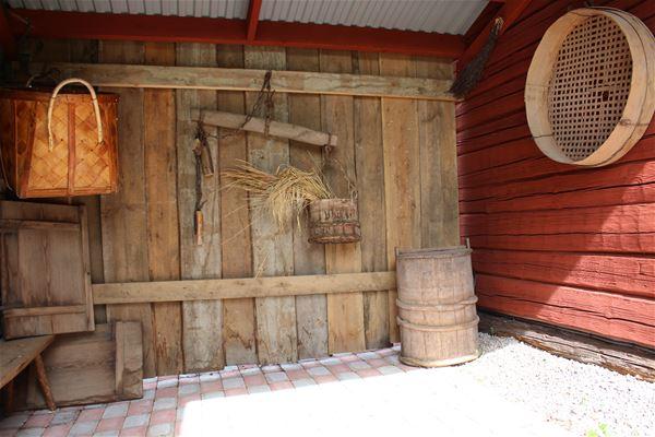 Gammal dörr och trätunna, flätad korg och gammalt såll.