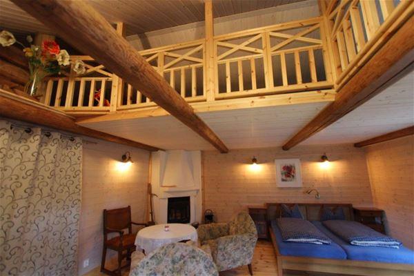 Interiörbild av stuga med dubbelsäng, öppenspis och loft.